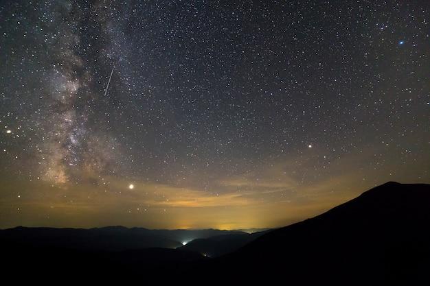 Nocny krajobraz gór z gwiazdami pokryte niebo.