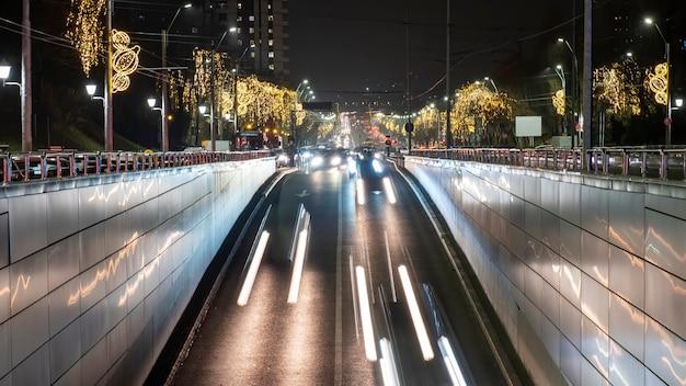 Nocny krajobraz miasta, wiele samochodów poruszających się po drodze w tunelu, dużo bożonarodzeniowej iluminacji, ślady świetlne w bukareszcie, rumunia
