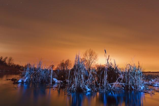 Nocny krajobraz w zamarzniętej rzece. światło słońca odbite w chmurach.