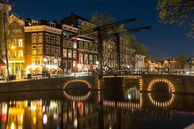 Nocny krajobraz z domami i kanałem w amsterdamie