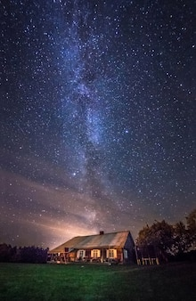 Nocny krajobraz z gwiazdami drogi mlecznej nad wiejskim domem poza miastem.