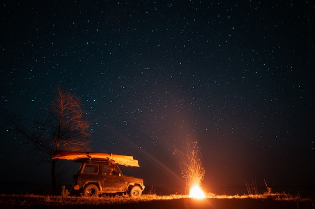 Nocny krajobraz z jasnym ogniskiem i samochodem