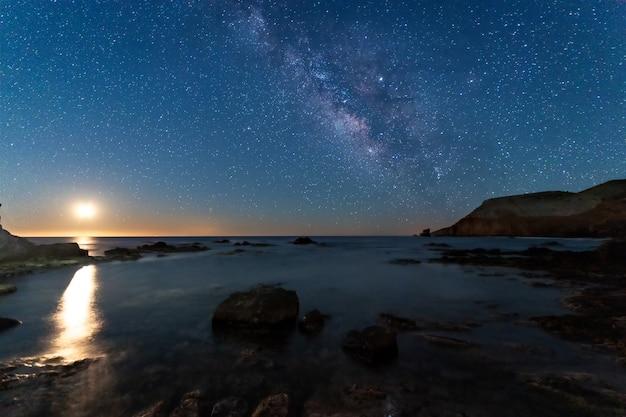 Nocny krajobraz z księżycem i drogą mleczną na wybrzeżu escullos. park przyrody cabo de gata. hiszpania.