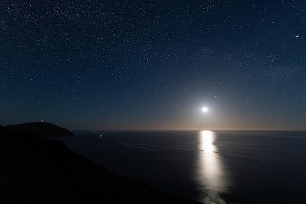 Nocny krajobraz z księżycem z punktu widzenia amatisty. park przyrody cabo de gata. hiszpania.