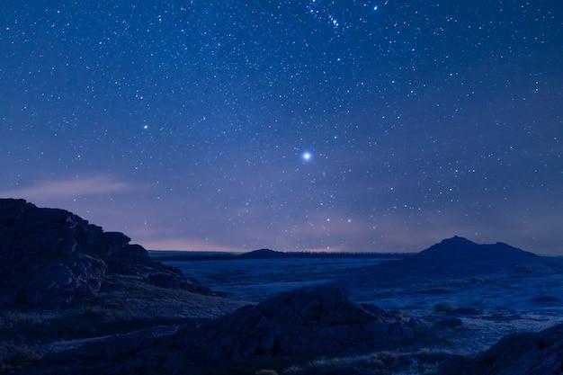 Nocny krajobraz z pięknymi górami i majestatycznym niebem gwiazd