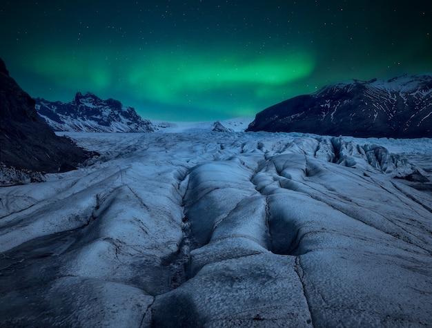 Nocny lodowiec z zorzą polarną na niebie.