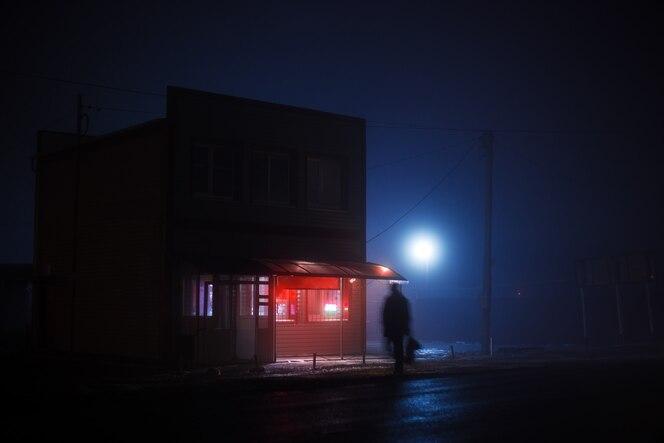 Nocny niebieski mglisty krajobraz. na poboczu stoi sklepik z podświetlanym na czerwono szyldem, przez jezdnię przecina tłusta sylwetka mężczyzny.
