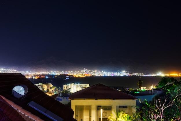 Nocny panoramiczny widok na plażę nad morzem czerwonym w ejlacie słynny kurort i miasto rekreacyjne w miastach izrael i akaba - jordan