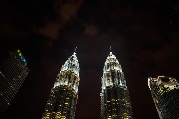 Nocny pejzaż ze słynnymi bliźniaczymi wieżami petrochemical company petronas w kuala lumpur