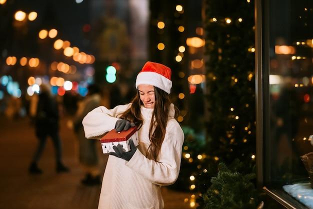 Nocny portret ulicy młodej pięknej kobiety działającej podekscytowany. świąteczne lampki do girland.