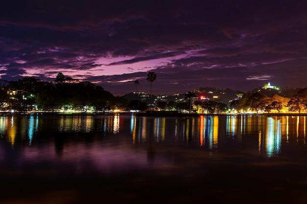 Nocny teren rekreacyjny w jeziorze parkowym. odbicie lampionów w wodzie.