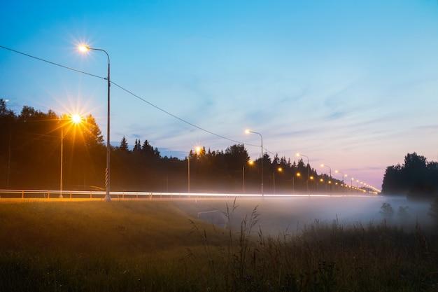 Nocny tor wiejski z latarniami i mgłą.
