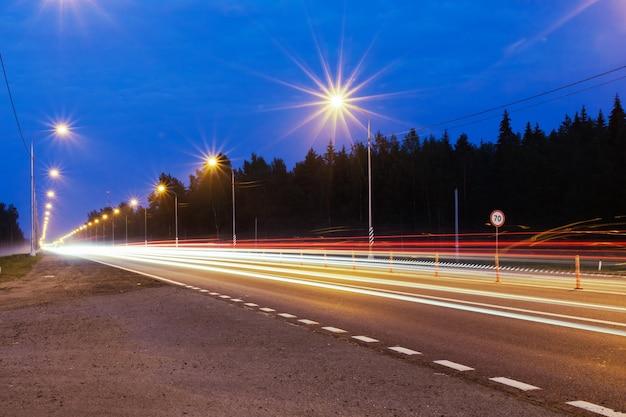 Nocny tor z latarniami i rozmytymi światłami poruszających się samochodów.