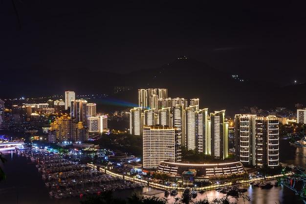 Nocny widok miasta sanya z jasnym wielokolorowym oświetleniem budynków, konstrukcji, dróg, chodników, słupów, mostów. sanya, hajnan, chiny