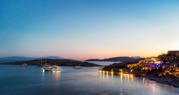 Nocny widok na dużą oświetloną łódź w pobliżu luksusowego kurortu odkryty kurort na europejskich wyspach turystycznych