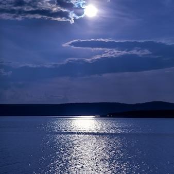 Nocny widok na jezioro, niebo z dramatycznymi chmurami i księżyc w pełni