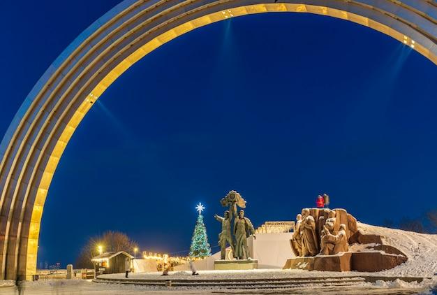 Nocny widok na łuk przyjaźni narodów w kijowie na ukrainie