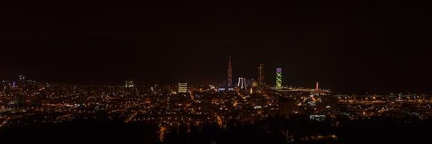 Nocny widok na panoramę miasta. uniwersytet technologiczny czarnomorski, hotel radisson blu, wieża porta batumi, wieża alfabetu i port