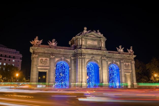Nocny widok na puerta de alcala w madrycie udekorowany na boże narodzenie