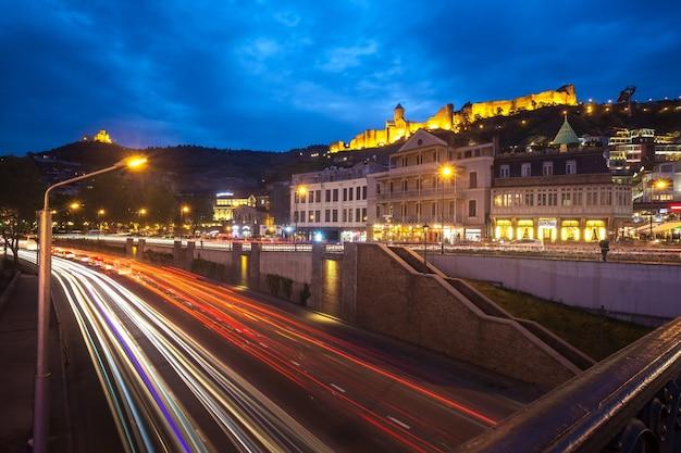 Nocny widok na tbilisi, jasne światła twierdzy narikala i stare miasto w tbilisi.
