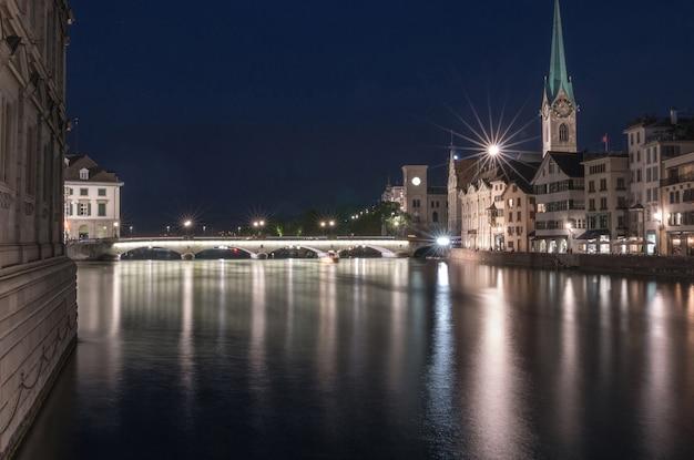 Nocny widok na zabytkowe centrum zurychu ze słynnym kościołem fraumunster, kanton zurych, szwajcaria. wieczorny letni dzień