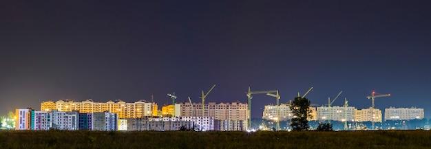 Nocny widok panoramy wielu dźwigów budowlanych na budowie nowej nowoczesnej dzielnicy mieszkalnej