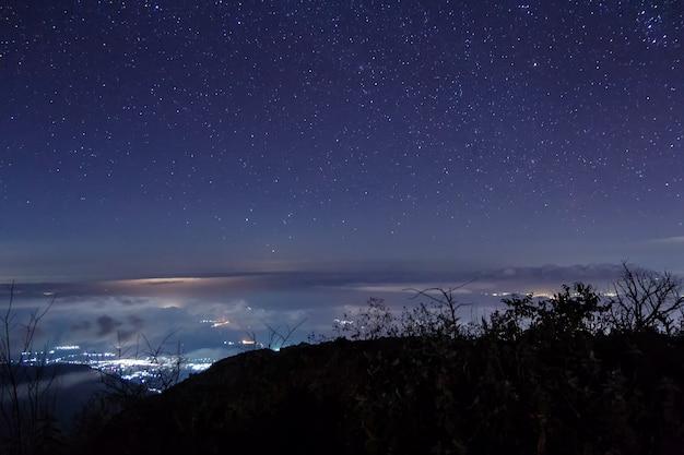 Nocny widok z gwiazdami nad chmurami i górą