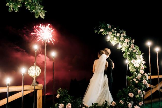 Nocny wieczór jest tłem. ogólny plan wzrostu. na weselu nowożeńcy widzą piękny salut na niebie.