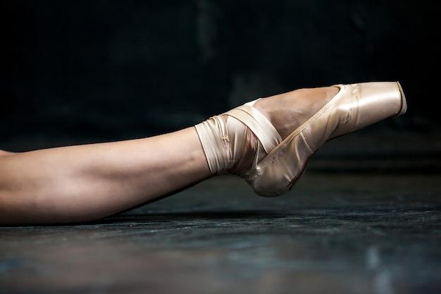 Noga baleriny z bliska w pointes na czarnej drewnianej podłodze