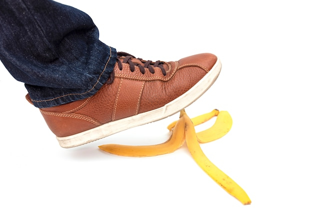 Noga człowieka wchodzącego na skórkę od banana, zdjęcie koncepcyjne
