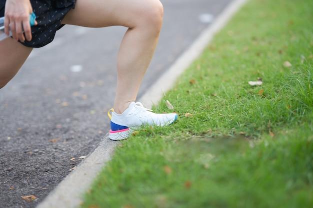 Noga kobieta na rozciąganie mięśni przed ćwiczeniami w godzinach porannych