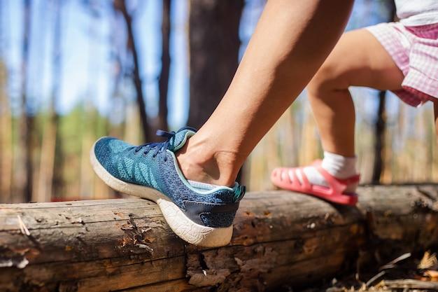 Noga kobiety i noga dziecka na tle lasu. piesze wycieczki, las z rodziną.