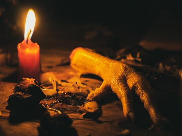 Noga kurczaka do różnych magicznych rytuałów i wróżb. świece palą się na starym stole. atrybuty okultyzmu i magii.