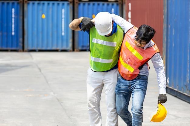 Noga pracownika zraniona lub omdlona z powodu stresu i ciężkiej pracy, wsparcie przyjaciela pomaga w chodzeniu po pierwszą pomoc.