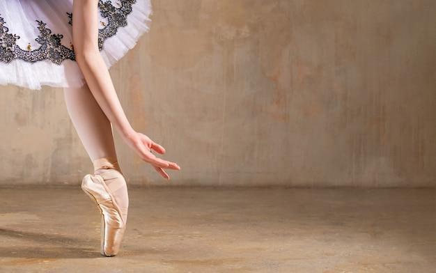 Noga w pointe pod tutu i dłonie baleriny