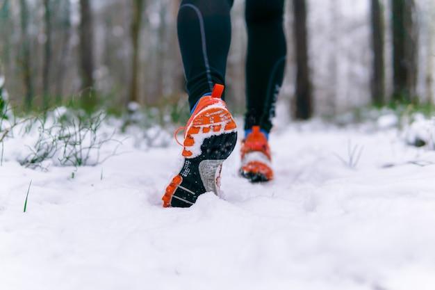 Nogi biegacza w tenisówkach podczas biegania zimą po zaśnieżonej ścieżce w parku