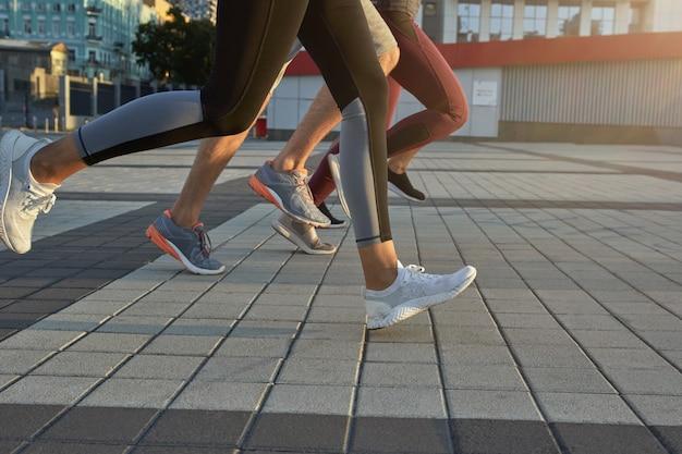 Nogi biegaczy w strojach sportowych