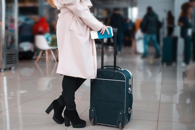 Nogi bizneswoman z bagażem na lotnisku.