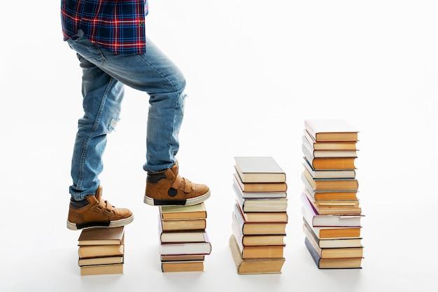Nogi chłopca w dżinsach na stosach książek. kroki z literatury. biała przestrzeń. miejsce na tekst. wiedza i edukacja.