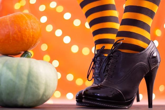 Nogi czarownicy w pasiastych pończochach i szpilkach z dyniami na pomarańczowym tle, bokeh. halloween. skopiuj miejsce.