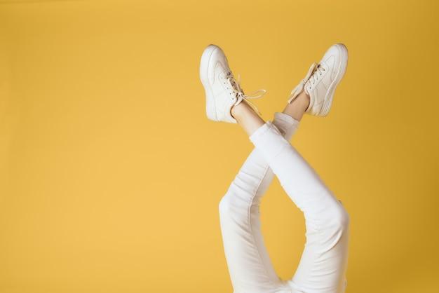 Nogi damskie białe spodnie i trampki studio mody elegancki styl