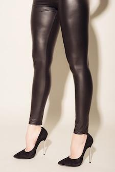 Nogi damskie w czarnych obcisłych skórzanych spodniach i butach na wysokim obcasie na szarym