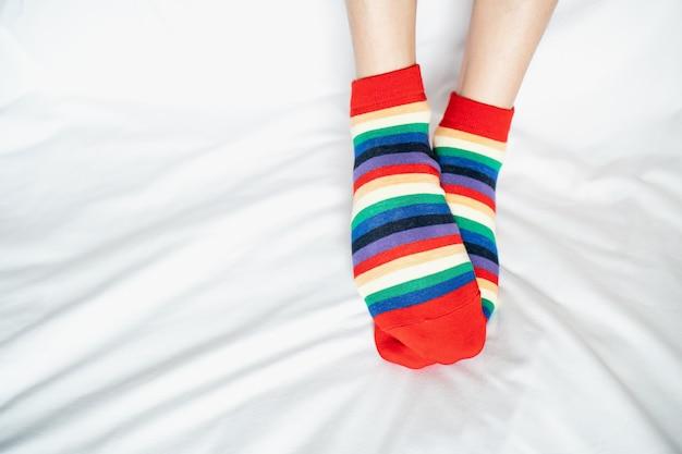 Nogi damskie w naprzemiennych kolorach skarpet, boczny stojak na białej tkaninie.