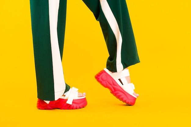 Nogi damskie w sportowych sandałach z czerwoną podeszwą i zielonymi spodniami w paski