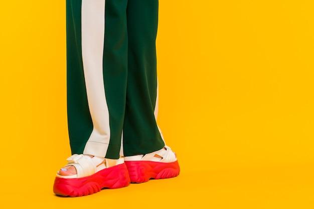 Nogi damskie w sportowych sandałach z czerwonymi podeszwami i zielonych spodniach w paski na żółtym tle.
