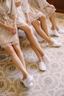 Nogi druhen w szlafrokach i kapciach siedzących na łóżku