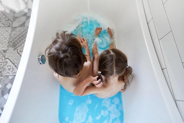 Nogi dziecka w wannie kąpiące się w niebieskiej wodzie