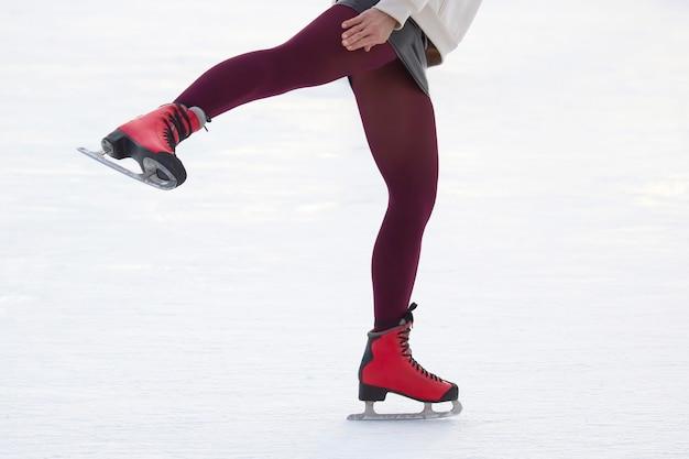 Nogi dziewczyny na łyżwach na lodowisku