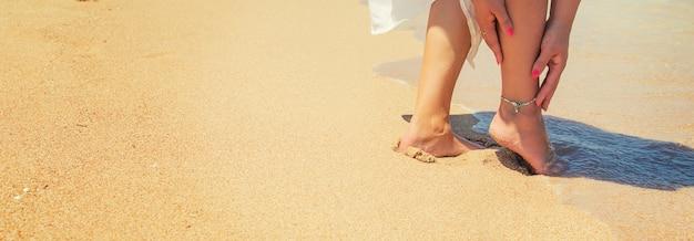 Nogi dziewczyny nad brzegiem morza.