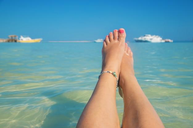 Nogi dziewczyny nad brzegiem morza